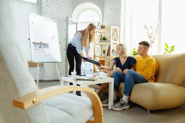 Innenarchitekt, der mit jungem paar arbeitet. schöne familie und professioneller designer oder architekt, der das konzept des zukünftigen interieurs bespricht und mit farbpalette, raumzeichnungen im modernen büro arbeitet. Kostenlose Fotos