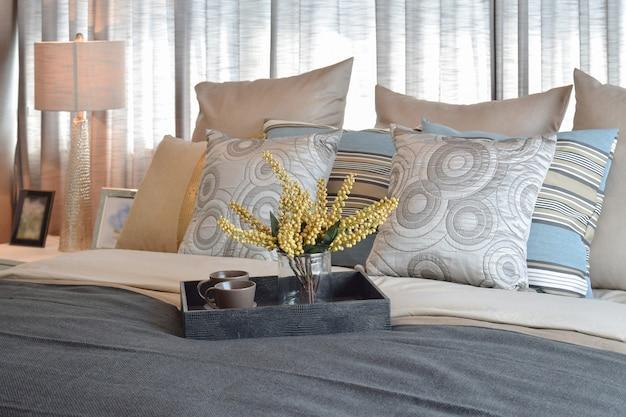 Innenarchitektur des luxusschlafzimmers mit gestreiften kissen und dekorativem teesatz auf bett Premium Fotos
