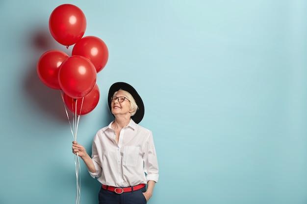 Innenaufnahme der angenehm aussehenden fröhlichen frau des alters hält helium-luftballons, kommt auf party für ältere menschen, um ihrer besten freundin zu gratulieren, konzentriert oben, trägt modische kleidung Kostenlose Fotos