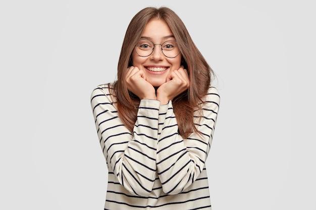 Innenaufnahme der glücklichen jungen frau mit brille, die gegen die weiße wand aufwirft Kostenlose Fotos