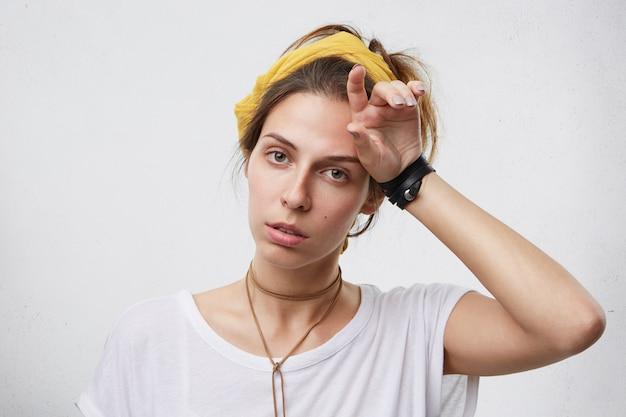 Innenaufnahme der müden frau in der freizeitkleidung, die ihre hand auf kopf hält. erschöpfte hausfrau, die erschöpft aussieht Kostenlose Fotos