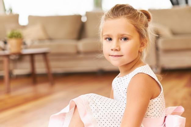 Innenaufnahme der niedlichen kleinen prinzessin, die schönes rosa kleid trägt, das auf boden zu hause sitzt und sich auf kinderleistung im kindergarten mit entzückenden blauen augen vorbereitet Kostenlose Fotos