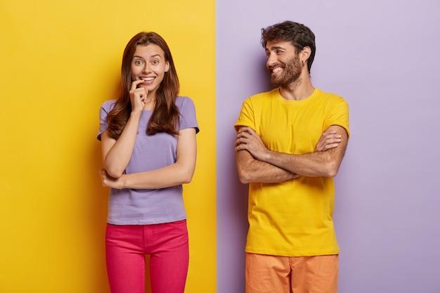 Innenaufnahme der positiven jungen frau und des mannes lächeln glücklich, gut gelaunt, verbringen freizeit zusammen, tragen t-shirts Kostenlose Fotos