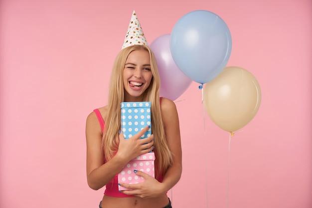 Innenaufnahme der positiven jungen langhaarigen frau, die sich freut, während sie in den bunten luftballons aufwirft, spaß auf der geburtstagsfeier hat und geschenke hält, die über rosa hintergrund stehen Kostenlose Fotos