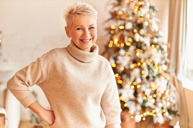 Innenaufnahme der schönen überglücklichen reifen frau mit blonden pixie-haaren, die am geschmückten weihnachtsbaum aufwerfen, kuscheligen pullover tragen, bereit zum feiern, lächeln und positive festliche stimmung haben Kostenlose Fotos
