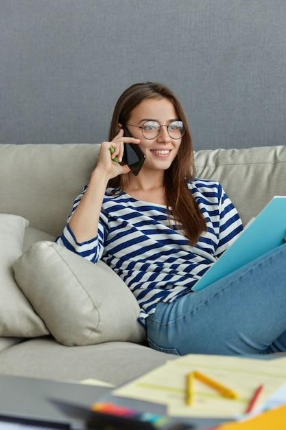 Innenaufnahme der zufriedenen frau hat telefongespräch, während sie auf dem bequemen sofa sitzt, finanzbericht bespricht, matrosenpullover, jeans und brille trägt, fröhlich lächelt, fernarbeit genießt Kostenlose Fotos