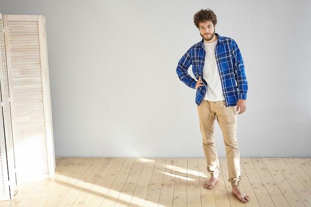 Innenaufnahme des attraktiven modischen jungen europäischen bärtigen männlichen modells, das trendige beige jeans und kariertes blaues hemd trägt, das barfuß auf holzboden zu hause posiert und hand auf seiner taille hält Kostenlose Fotos