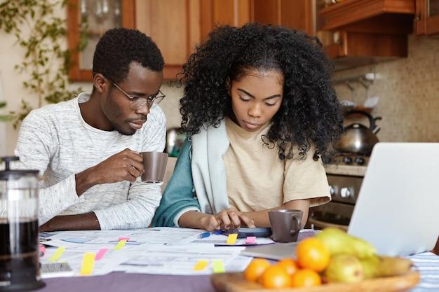 Innenaufnahme des ernsten afrikanischen mädchens unter verwendung des taschenrechners beim bezahlen von rechnungen, sitzend am küchentisch Kostenlose Fotos