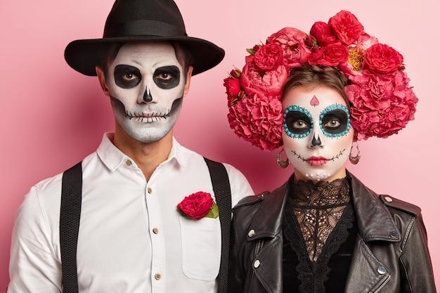 Innenaufnahme des ernsthaften romantischen paares posieren vor halloween-ereignis, tragen blumenkranz und hut auf köpfen, traditionelle gruselige kostüme, schauen direkt in die kamera, haben zombie-make-up im mexikanischen stil Kostenlose Fotos