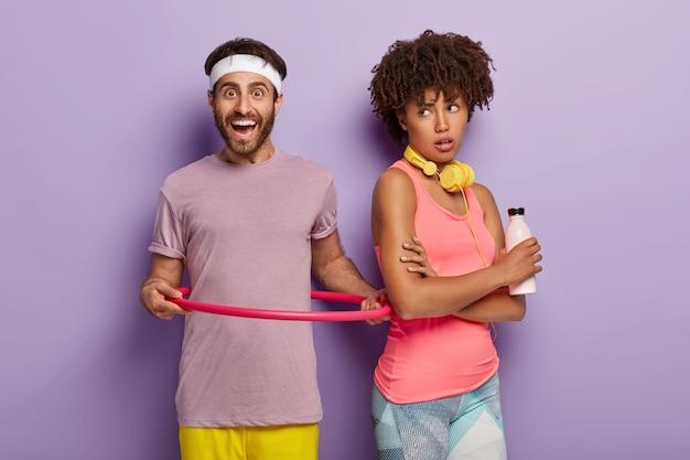 Innenaufnahme des lächelnden mannes dreht hula hoop, gekleidet in lila t-shirt, in guter körperlicher verfassung, afro-frau tritt zurück, hält flasche frisches wasser, isoliert über lila wand. gesunder lebensstil Kostenlose Fotos