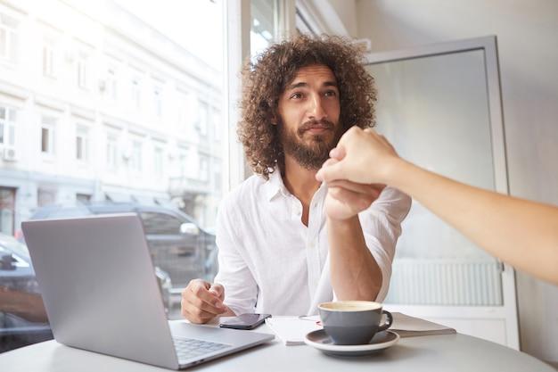 Innenaufnahme des reizenden jungen bärtigen mannes mit dem langen lockigen haar, das am fenster im kaffeehaus sitzt, außerhalb des büros mit laptop arbeitet und weibliche hand im gruß schüttelt Kostenlose Fotos