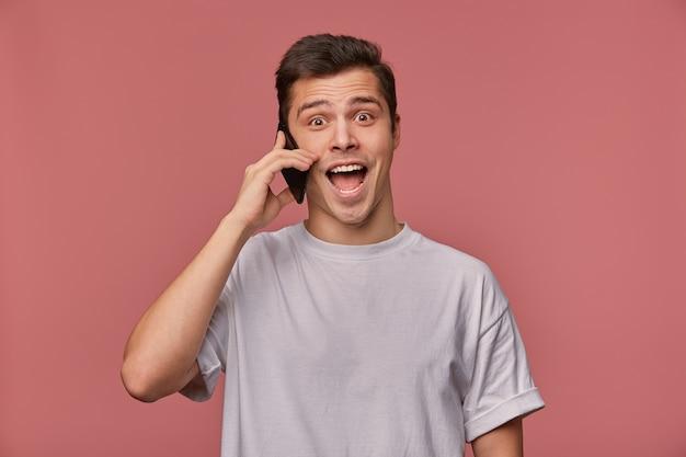 Innenaufnahme des überglücklichen jungen mannes der braunen augen im grauen t-shirt, der über rosa hintergrund aufwirft, aufgeregtes gespräch am telefon hat und fröhlich zur kamera schaut Kostenlose Fotos