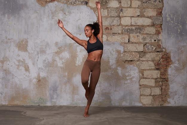 Innenaufnahme einer attraktiven jungen dunkelhäutigen dame mit braunem lockigem haar, die zeitgenössischen tanz einstudiert und konzentriert ist, während sie die hände unter dem kopf hält Kostenlose Fotos