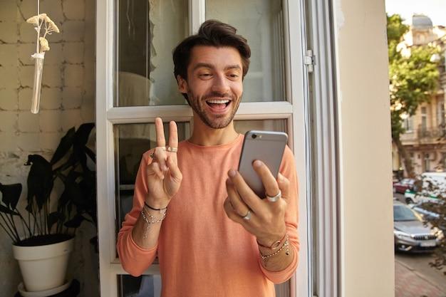 Innenaufnahme eines attraktiven jungen mannes mit bart, der sich auf geöffnetes fenster stützt, während er mit seinen freunden videochat hat, fröhlich lächelt und friedensgeste zeigt Kostenlose Fotos