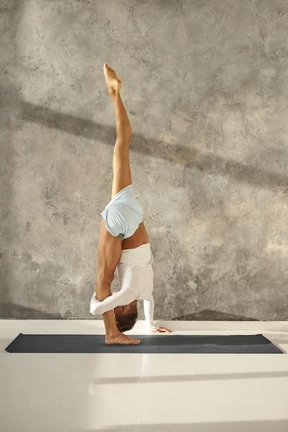 Innenaufnahme in voller länge eines nicht erkennbaren sportlichen muskulösen mannes in sportbekleidung, der yoga praktiziert, eine stehende split-pose macht oder urdhva prasarita eka padasana, kniesehnen, waden und oberschenkel streckt Kostenlose Fotos