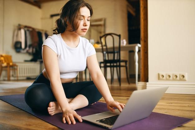 Innenbild der niedlichen jungen frau der übergröße, die auf matte vor offenem laptop sitzt, online-video-tutorial durch professionellen fitnesstrainer beobachtend, von zu hause aus wegen sozialer distanzierung trainierend Kostenlose Fotos