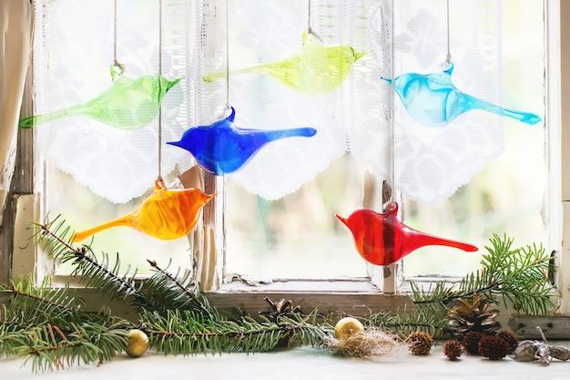 Innenfenster mit glasvögeln und weihnachtsbaum Premium Fotos
