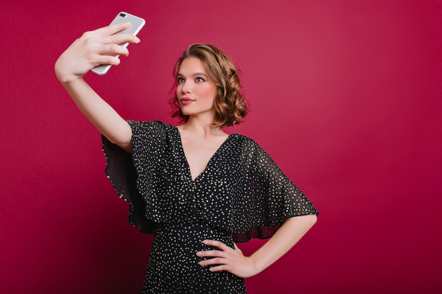 Innenfoto der attraktiven jungen dame im weinlesekleid, das selfie auf bordeauxrotem hintergrund macht Kostenlose Fotos