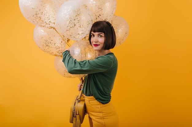 Innenfoto der herrlichen kaukasischen dame, die geburtstag feiert. porträt des erstaunlichen braunhaarigen mädchens im grünen pullover, der mit luftballons steht. Kostenlose Fotos