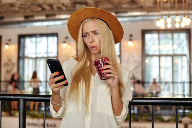 Innenfoto der schönen verwirrten frau mit den langen haaren, die über restaurantinnenraum mit tasse limonade in der hand aufwerfen, ihr handy betrachten und nachrichten lesen Kostenlose Fotos