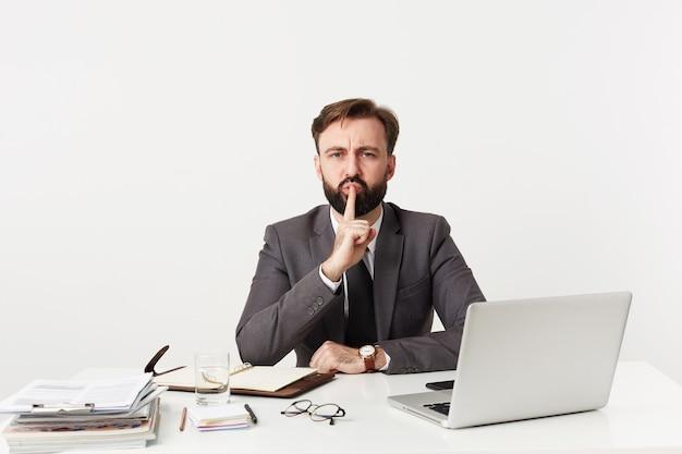 Innenfoto des ernsten jungen bärtigen geschäftsmannes, der im büro mit seinem laptop und notizbuch arbeitet, am tisch über weißer wand sitzt und hand in stiller geste hebt Kostenlose Fotos