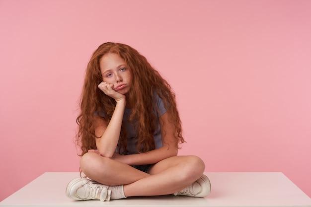 Innenfoto des weiblichen kindes mit dem gelockten foxy haar, das kopf auf erhabener hand lehnt, während mit gekreuzten beinen über rosa hintergrund in freizeitkleidung sitzt und kamera mit gelangweiltem gesicht betrachtet Kostenlose Fotos