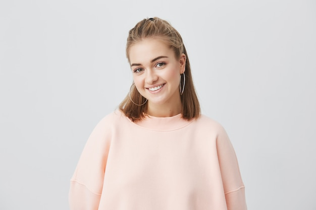 Innenporträt der schönen jungen kaukasischen frau mit dem glatten blonden haar, das fröhlich lächelt und ihre weißen zähne zur kamera zeigt, während sie sich an ihren freien tagen glücklich und sorglos fühlen Kostenlose Fotos