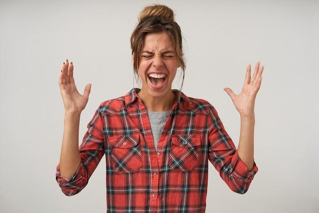 Innenporträt der wütenden jungen schönen frau, die mit erhobenen händen steht, heftig schreit, kariertes hemd und brötchenfrisur trägt Kostenlose Fotos