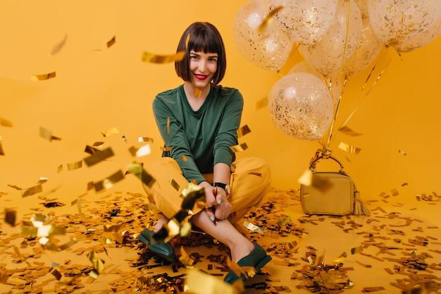 Innenporträt des angenehmen brünetten mädchens, das auf konfetti sitzt. fröhliche europäische dame im grünen pullover posiert. Kostenlose Fotos