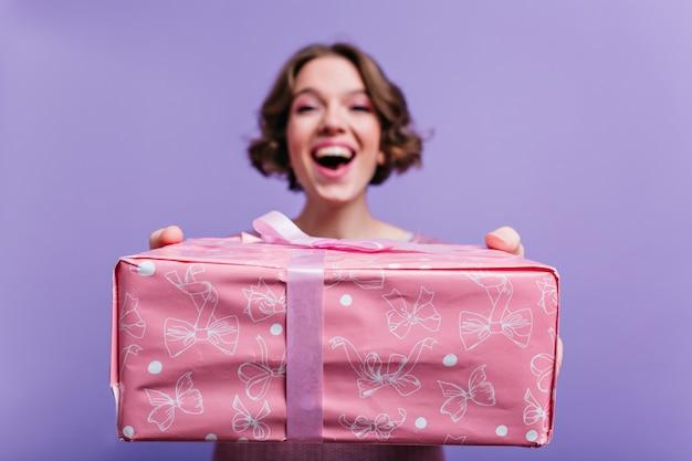 Innenporträt des glückseligen kurzhaarigen mädchens mit rosa geschenkbox auf vordergrund. unscharfes foto der lächelnden brünetten frau auf lila wand mit weihnachtsgeschenk im fokus. Kostenlose Fotos