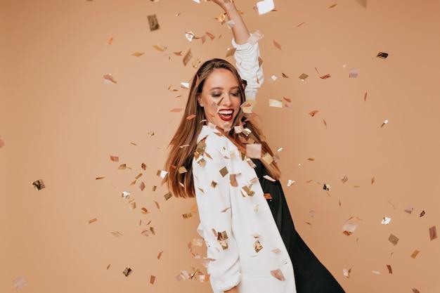 Innenporträt des hübschen jungen weiblichen modells mit hellbraunem haar, das weiße jacke und schwarzes kleid trägt, das tanzt und spaß auf beiger wand mit konfetti hat Kostenlose Fotos