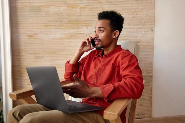 Innenporträt des jungen kurzhaarigen bärtigen kerls mit der dunklen haut, die telefongespräch beim sitzen vor dem fenster im stuhl, außerhalb des büros arbeitend hat Kostenlose Fotos