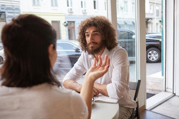 Innenporträt des schönen lockigen mannes mit bart, der sich im café trifft, aufmerksam und ruhig auf frau neben ihm schaut, am tisch am fenster sitzend Kostenlose Fotos