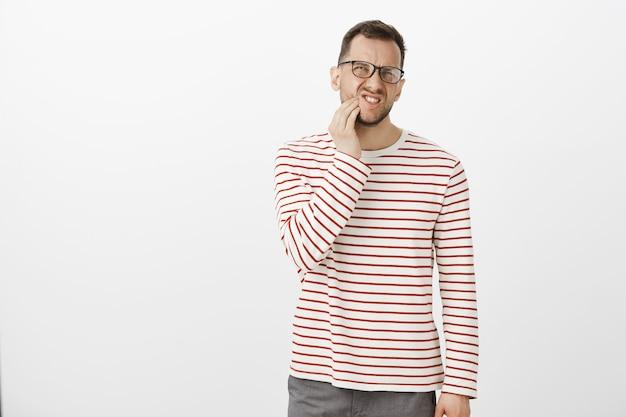 Innenporträt eines unzufriedenen unbequemen europäischen mannes in brille, der unter zahnschmerzen leidet Kostenlose Fotos