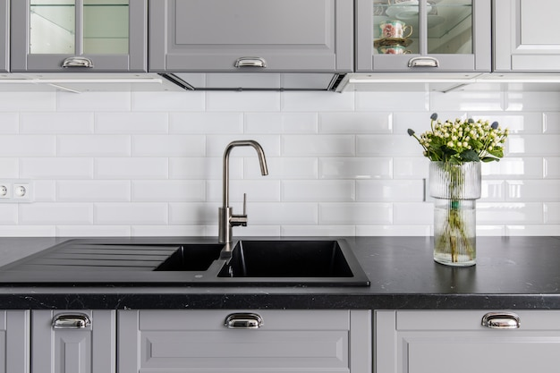 Innenraum der modernen küche. dunkle arbeitsplatte und waschbecken, graue schließfachfronten. vase mit blumen schmückt den tisch Premium Fotos