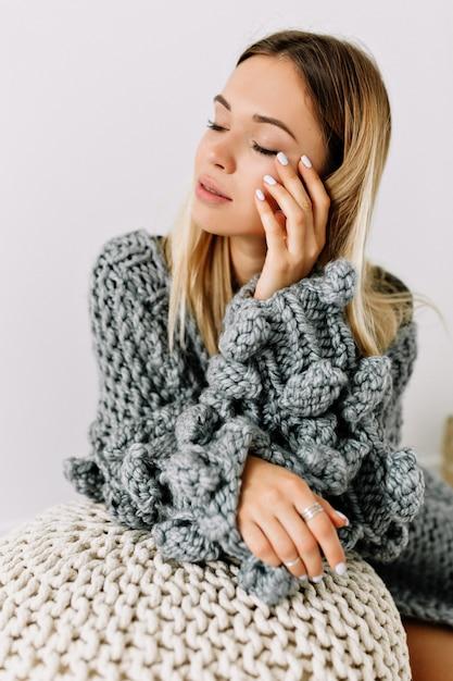Innenstudioaufnahme der reizenden sinnlichen frau mit den blonden haaren und den geschlossenen augen, die ihr gesicht berührend strickpullover berühren, der im weißen raum posiert Kostenlose Fotos