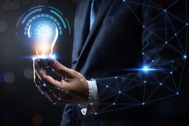 Innovation und energie des kreativen denkens, geschäftsmann, der die glühlampe glüht und beleuchtet mit verbindung zum menschlichen körper und zum energieleben hält Premium Fotos