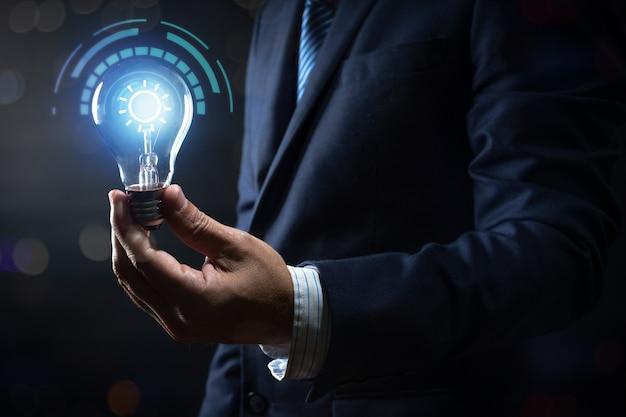 Innovation und energie des kreativen denkens, geschäftsmann, der die glühlampe glüht und mit verbindung beleuchtet hält Premium Fotos