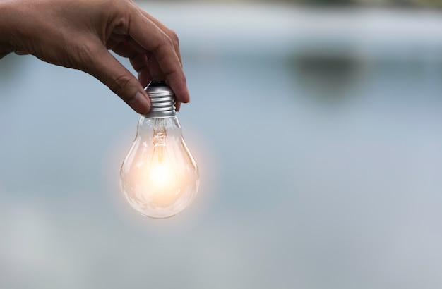Innovation und kreatives konzept der hand halten eine glühbirne Premium Fotos