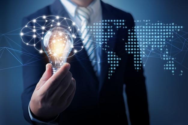 Innovations- und technologiekonzept, geschäftsmann, der das halten der glühlampe kreativ mit verbindungslinie hält, um mit internet-anzeige zu kommunizieren, erneuern und entwickeln unbegrenzte leute Premium Fotos