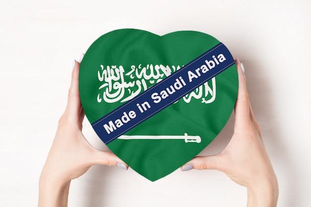 Inschrift made in saudi-arabien die flagge von saudi-arabien. weibliche hände, die einen geformten kasten des herzens halten. Premium Fotos