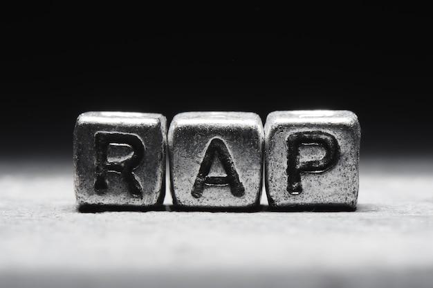 Inschrift rap auf metallwürfeln im schmutzstil auf einem schwarzen hintergrund lokalisiert Premium Fotos