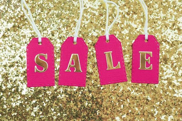 Inschrift verkauf in goldenen buchstaben auf rosa etiketten mit weißen seilen auf goldenem grund mit einem glitzer. Premium Fotos