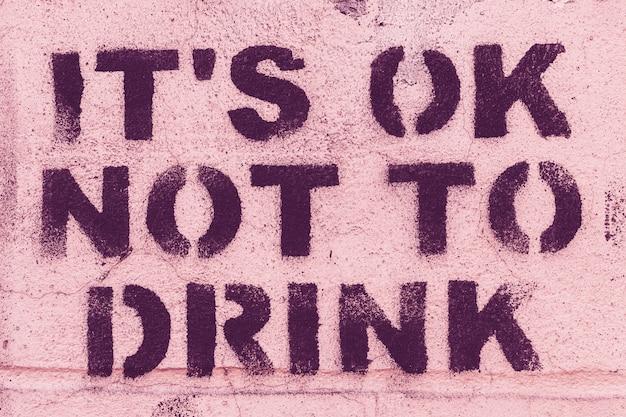 Inschrift von lila buchstaben an einer rosa wand - es ist in ordnung, nicht zu trinken. Premium Fotos