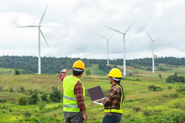 Inspektion mit zwei windmühleningenieuren und fortschritt überprüfen windkraftanlage an der baustelle, indem sie ein auto als fahrzeug verwenden. Premium Fotos