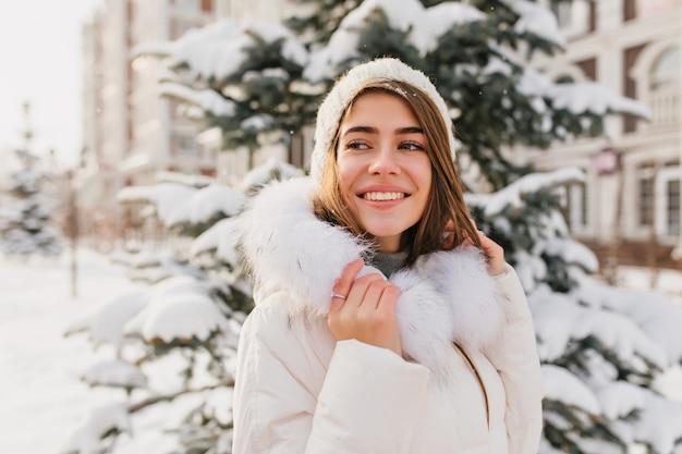 Inspirierte europäische dame trägt weiße winterkleidung, die naturansichten genießt. außenporträt des atemberaubenden kaukasischen weiblichen modells lächelnd Kostenlose Fotos