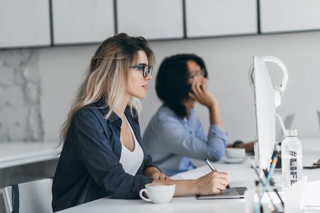 Inspirierte freiberufliche webdesignerin mit tablet und stift, die auf den bildschirm schaut, während ihre freundin telefoniert. asiatischer student, der smartphone hält und auf tastatur tippt und neben blondem mädchen sitzt. Kostenlose Fotos