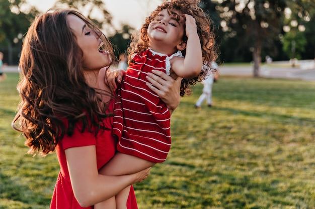 Inspirierte junge mutter, die tochter mit lächeln betrachtet. außenporträt der glücklichen familie, die sommerwochenende im park genießt. Kostenlose Fotos