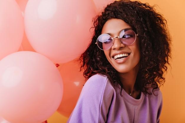 Inspiriertes afrikanisches mädchen, das gute gefühle in ihrem geburtstag ausdrückt. blithesome lockige dame, die mit rosa luftballons aufwirft. Kostenlose Fotos