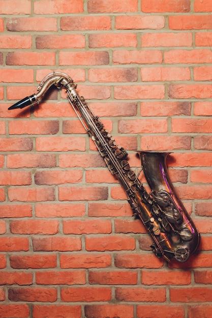 Instrument der klassischen musik des saxophons auf maurerarbeitwand Premium Fotos